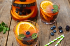 Berry sangria - summer cocktail, decorated with berries, orange and mint